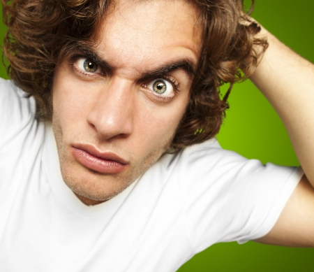 confus: portrait de jeune homme � la recherche confuse sur fond vert Banque d'images