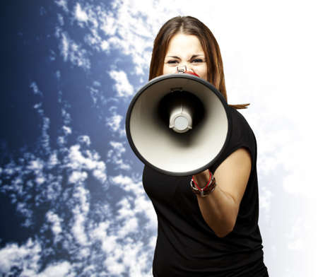 portrait of young woman shouting with megaphone against a cloudy sky background photo