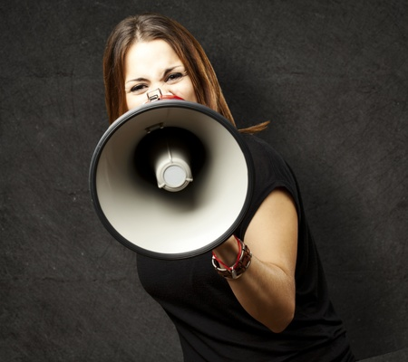 portrait of young woman shouting with megaphone against a grunge wall photo