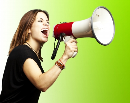 woman screaming: portrait of young girl shouting with megaphone over green background Stock Photo