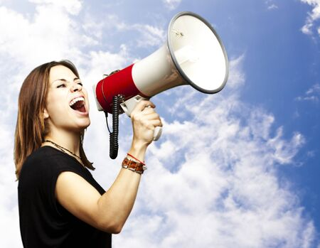 news stand: portrait of young woman shouting with megaphone against a blue background Stock Photo