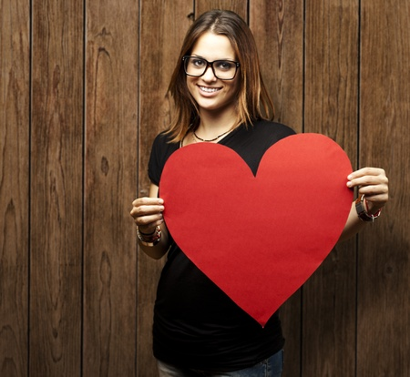 holding sign: portrait of a pretty woman holding a paper heart against a wooden wall