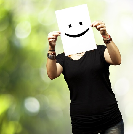 Woman showing a blank paper with a smile emoticon in front of her face against a nature background photo