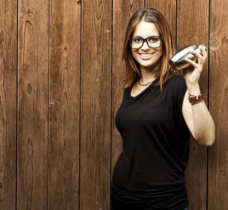 portrait of young woman with cocktail shaker against a wooden wall photo