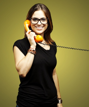 portrait of young woman talking using vintage telephone over beige background photo