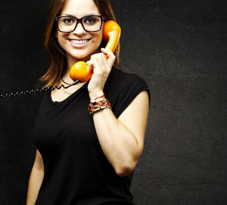 portrait of young woman talking using a vintage telephone against a grunge background Stock Photo - 13156162