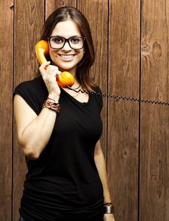 portrait of young woman talking on vintage telephone against a wooden wall photo