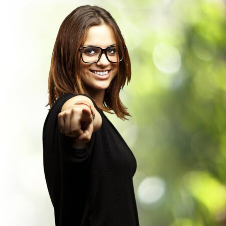 portrait of young woman pointing with finger against a nature background photo