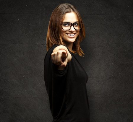 portrait of young woman pointing with finger against a grunge background photo