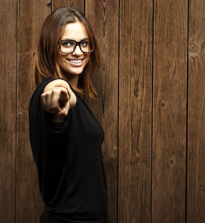 portrait of young woman pointing with finger against a wooden wall photo
