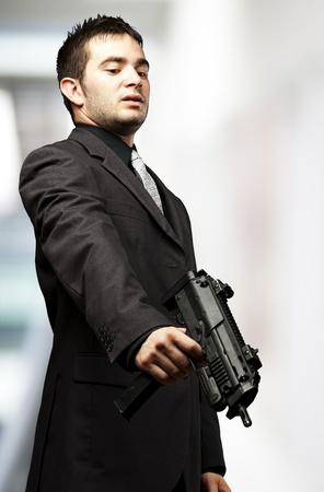 mafia man aiming down with gun against a indoor photo