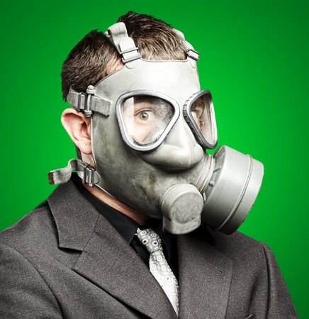 portrait of a business man with gas mask over green background Stock Photo - 12112233