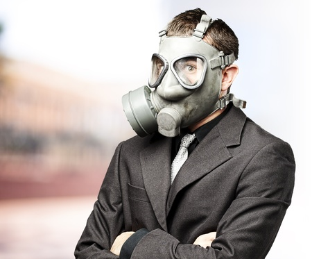 portrait of business man with gas mask against at outdoor photo
