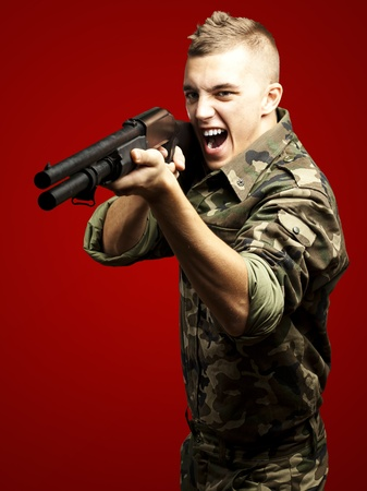 portrait of a young soldier aiming with shotgun against a red background photo
