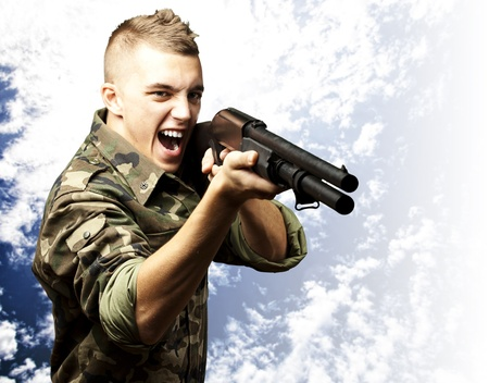 man holding gun: portrait of a young soldier aiming with shotgun against a cloudy sky background