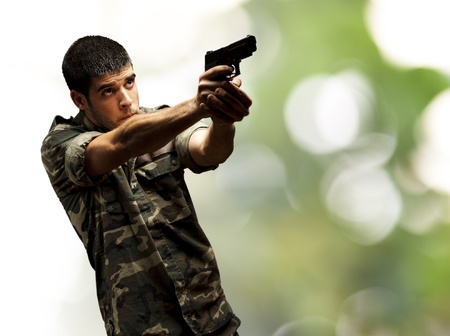 portrait of a young soldier aiming with pistol against a nature background photo