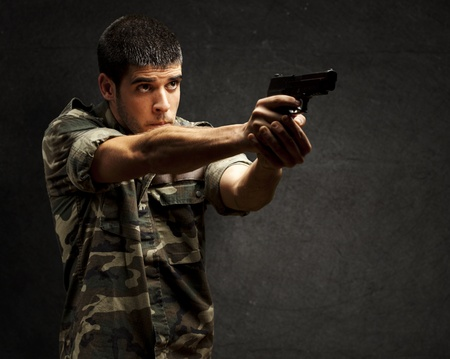 hombre disparando: retrato de un joven soldado apuntando con una pistola contra una pared del grunge Foto de archivo