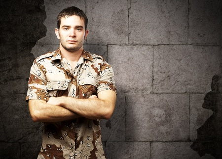 portrait of a serious young soldier standing against a vintage bricks wall Stock Photo - 13156201