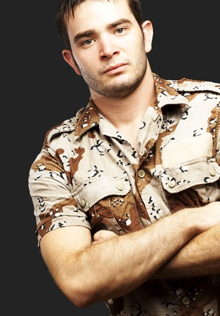 portrait of a serious young soldier standing against a black background Stock Photo - 13156068