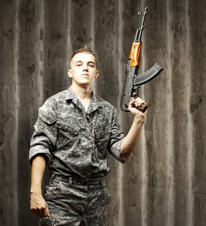 british man: portrait of young soldier holding rifle wearing urban camouflage against a grunge wooden wall