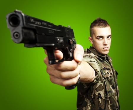 Portret van Kaukasische soldaat met jungle camouflage wijst met pistool over groene achtergrond