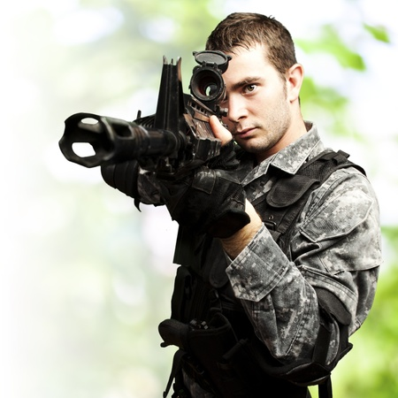 portrait of young soldier aiming with rifle against a jungle background Stock Photo - 13156037