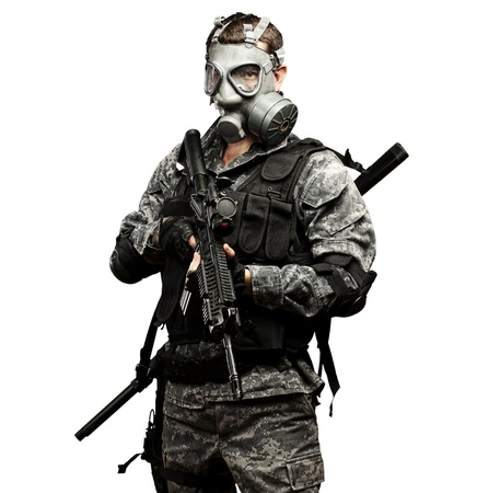 portrait of young soldier with gas mask and rifle against a white background photo