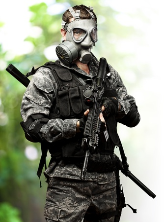 portrait of young soldier with gas mask and rifle against a nature background photo