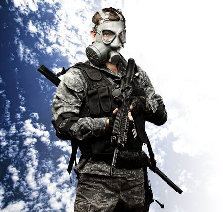 portrait of young soldier with gas mask and rifle against a cloudy sky background photo