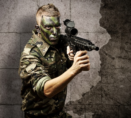 urban jungle: portrait of young soldier with jungle camouflage pointing with rifle against a grunge background