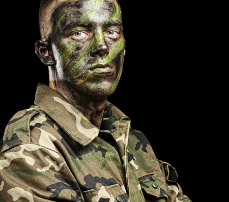 face guard: portrait of young soldier with jungle camouflage paint on a black background