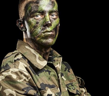 soldado: retrato de joven soldado con pintura de camuflaje selva, sobre un fondo negro Foto de archivo