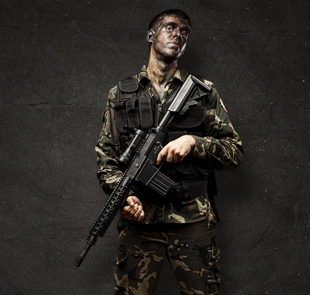 portrait of young soldier holding rifle against a grunge background photo