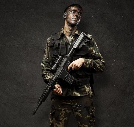 Retrato de joven con rifle de soldado contra un fondo del grunge