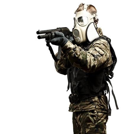 mascara gas: retrato de joven soldado con máscara de gas apuntando con la escopeta