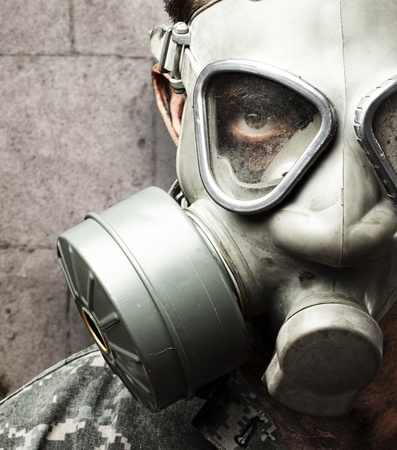respirator: portrait of young soldier wearing gas mask against a grunge bricks wall