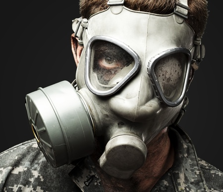 iraq war: portrait of young soldier wearing gas mask against a black background
