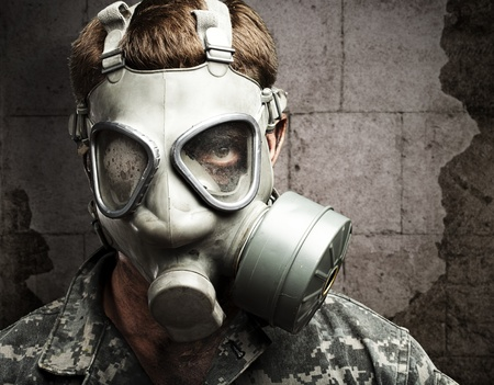 portrait of young soldier wearing gas mask against a vintage wall photo