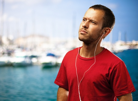 young man listen to music near the harbour photo