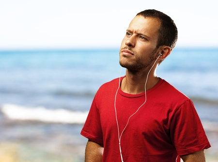 young man listen to music near the beach photo