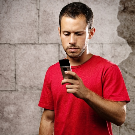 young man typing on mobile phone against a bricks wall  photo