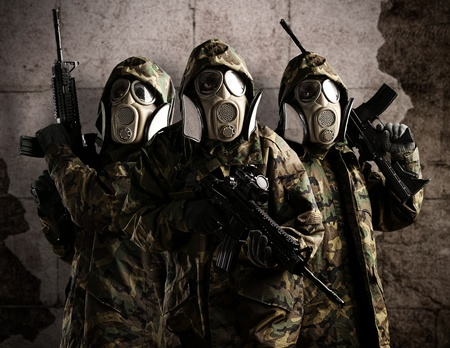 armed services: Tree armed soldiers with gas mask and rifles against a grunge bricks wall Stock Photo