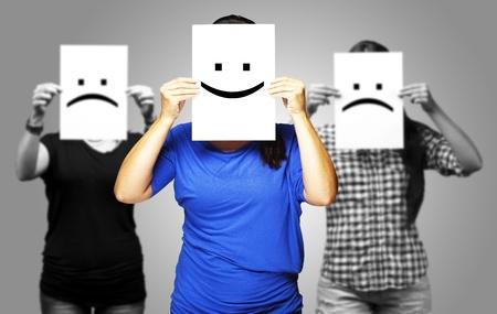 caras tristes: retrato de una mujer feliz en frente de dos womans tristes Foto de archivo