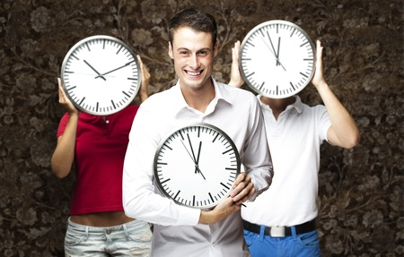 group of young students holding clock against a vintage wall photo
