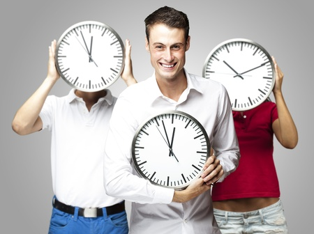 group of young students holding clock against a grey background photo