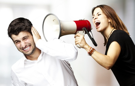 agitation: young woman screaming a man with the megaphone against a abstract background Stock Photo