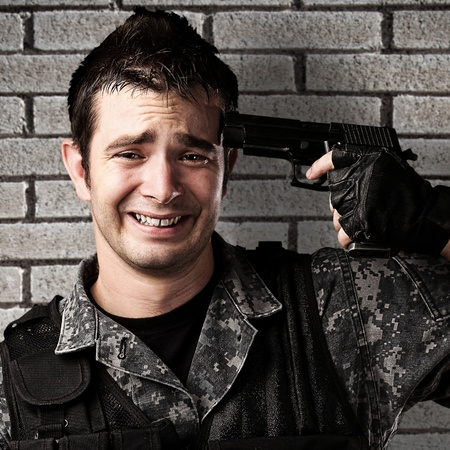 portrait of young soldier committing suicide against a grunge bricks wall photo