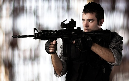 portrait of young soldier aiming with rifle against a blurred lights background photo