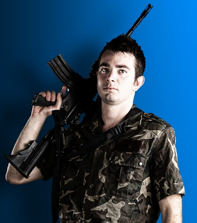 young soldier holding a rifle on a blue background photo