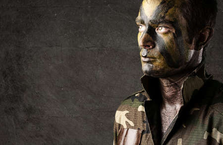 army man: portrait of young soldier face painted with jungle camouflage against a grunge wall